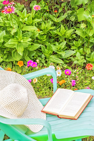day flowering: Relax with a book in the garden on a sunny summer day. Green chaise lounge and a white hat on a background of flowering flowerbed
