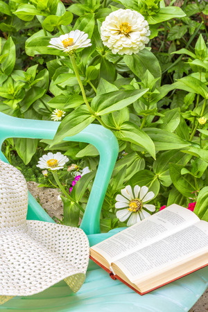 day flowering: Relax with a book in the garden on a sunny summer day. Green chaise lounge, a white hat and book on a background of flowering flowerbed