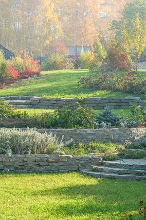 ajenjo: Paisaje de otoño con los céspedes verdes, muros de contención, macizos de flores y un fragmento de un tobogán alpino en el fondo de las hojas amarillas de los árboles de abedul en un día soleado Octubre por Foto de archivo