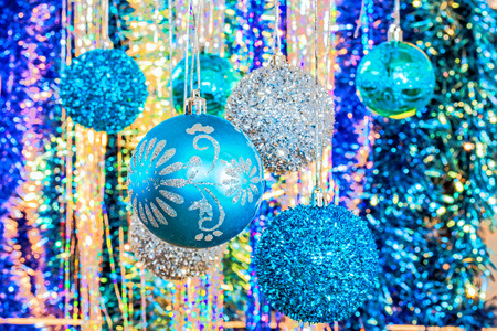Festive Christmas blue and silver balls on a soft background of tinsel, close-up. Selective focus Stock Photo
