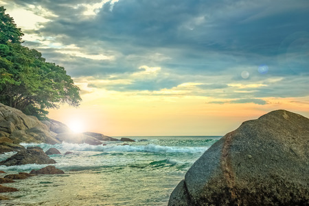 Landscape with rocks and rough sea at sunset on a background of storm clouds Stock Photo