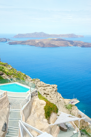 Pool with turquoise water on the rock of the Greek island of Santorini against the blue sea and sky