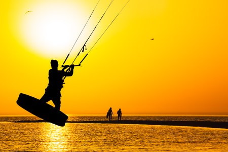 Silhouette of kitesurfer, jumping over the sea against a orange sunset Stock Photo