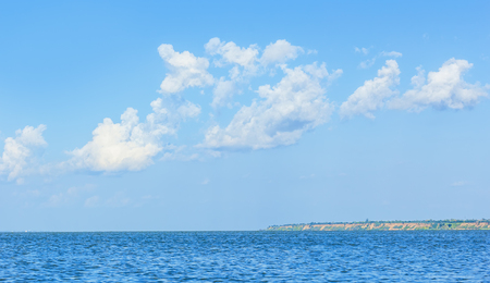 spit: Landscape with the sea, the distant shore and the blue sky with white clouds Stock Photo