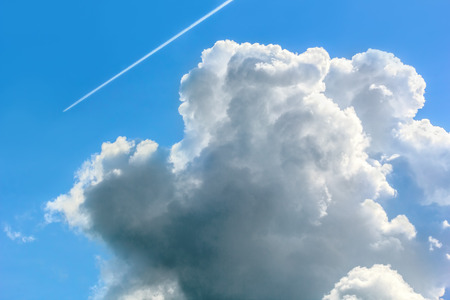 Blue sky with white cumulus cloud and contrail on a summer day, close-up Stock Photo