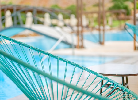 Blue chaise longue close up on a blurred pool background, Greece