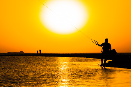 Silhouette of a surfer against the sea and picturesque orange sunset in summer evening