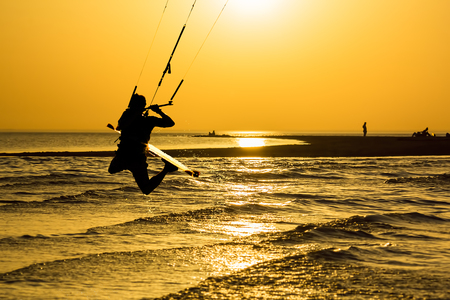 Silhouette of kitesurfer, jumping over the sea on the background of gold sunset