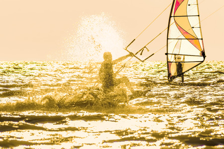 windsurf: Kitesurfing and windsurfing in the sea at sunset in the backlight