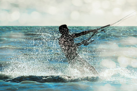 Surfer rushing through the sea in a spray cloud on the background of sunlight glare, close-up