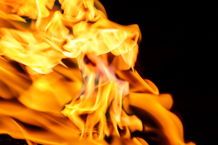 Texture of orange flame against a dark background, close up