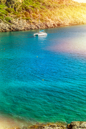 View of the sea bay and a sailing catamaran from a steep coast of the island of Crete, Greece Stock Photo