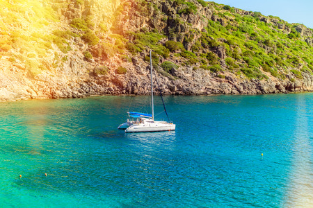 View of the sea bay and a sailing catamaran near a steep coast of the island of Crete, Greece 免版税图像 - 97238180
