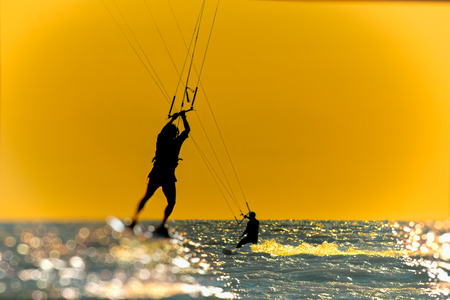 Silhouette of kitesurfer, jumping over the sea on sunset sky background. Photo toned Фото со стока