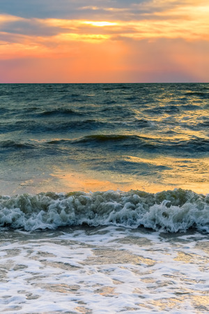 Seascape with a beautiful sunset over the sea waves in the summer evening