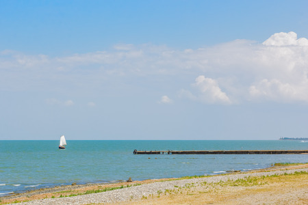 Deserted beach and sailing boat in the blue sea on a sunny summer day Stok Fotoğraf