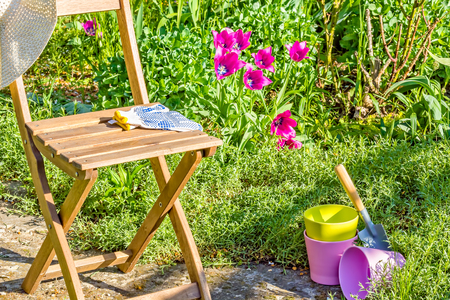 Spring work and relaxation in the sunny garden. Garden chair, hat, gloves, scoop and multi-colored flower pots next to the flowerbed