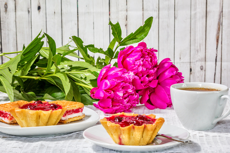 Tea drinking on a summer day. Still life with a cup of tea, cakes and a bouquet of red peonies on a white lace tablecloth on the background of wooden boards Reklamní fotografie