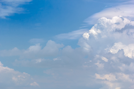Picturesque white cumulus clouds in the blue sky on a summer day, close-up