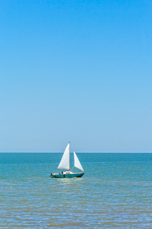 Sailboat in the blue sea against the cloudless sky on a summer day