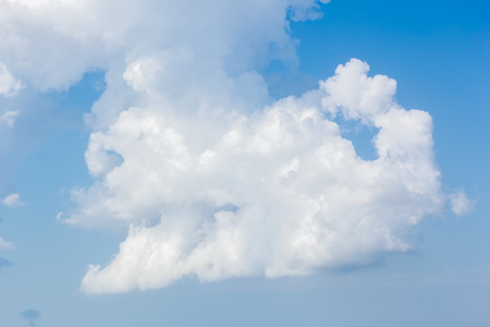Picturesque white cumulus cloud in the blue sky on a summer day, close-up