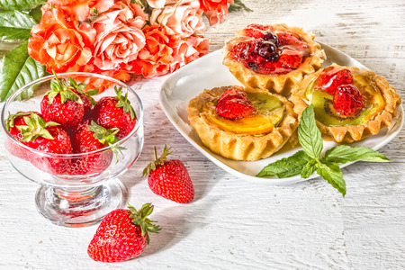 Still life with fruit cakes on a plate, red ripe strawberries in a glass ice-cream bowl and a bouquet of roses on a white wooden table, vintage Reklamní fotografie