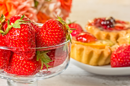 Still life with fruit cakes on a plate, red ripe strawberries in a glass ice-cream bowl and a bouquet of roses on a white wooden table, macro