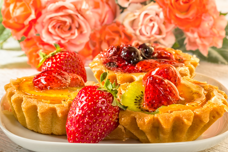 Still life with fruit cakes on a plate, red ripe strawberries and a bouquet of roses on a white wooden table, macro