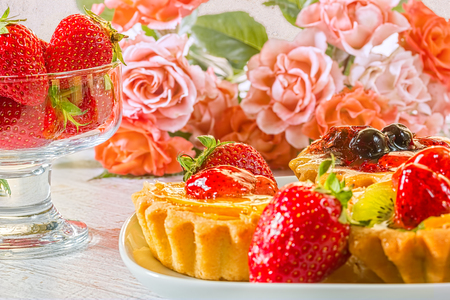 Still life with fruit cakes on a plate, red ripe strawberries in a glass ice-cream bowl and a bouquet of roses on a white wooden table, close-up