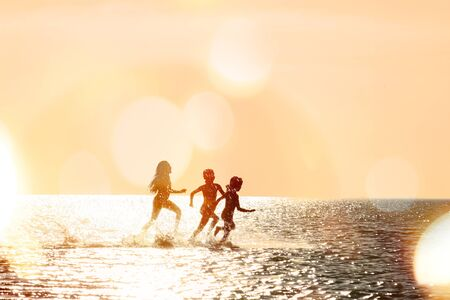 Silhouettes of children running through the water in the sea at sunset, backlit