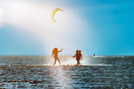 Silhouettes of children playing in the water on a summer evening against the blue sea and sky, backlight