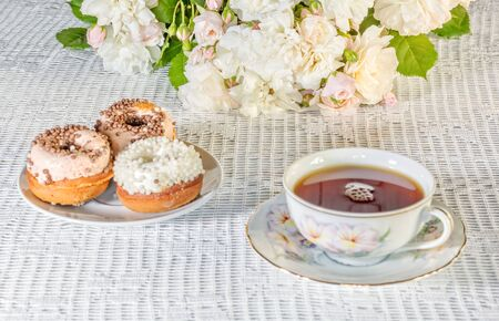 Tea drinking on a summer day. Still life with a cup of tea, cakes and a bouquet of white roses on a white lace tablecloth