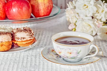 Tea drinking on a summer day. Still life with a cup of tea, cakes, red apples and a bouquet of white roses on a white lace tablecloth, close-up