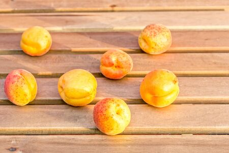 Ripe yellow orange apricots on a wooden table in the garden Reklamní fotografie