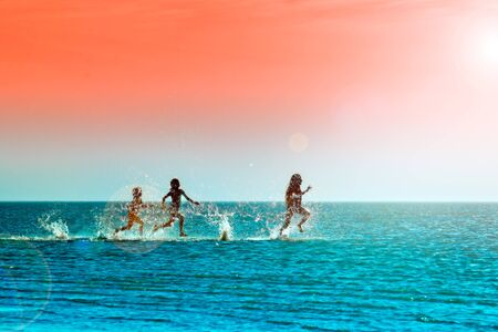 Silhouettes of children running through the water in the sea at sunset Reklamní fotografie