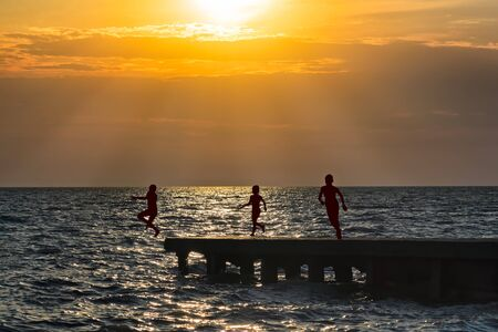 Silhouettes of children running on the breakwater and jumping into the sea against the orange sunset Reklamní fotografie
