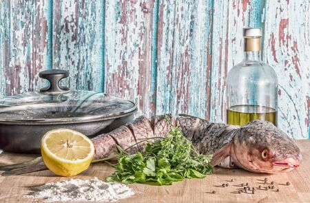 Still life with fresh raw fish of red-finned mullet for cooking with frying pan, lemon, parsley, spices, bottle of olive oil on a rustic background of old boards, vintage