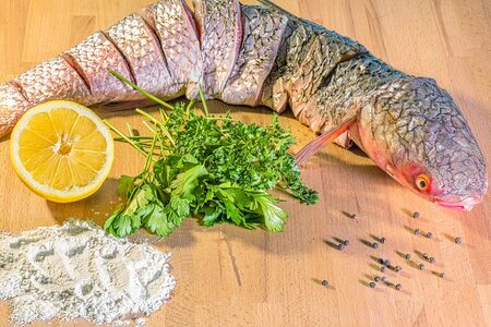 Fresh raw fish of red-finned mullet for cooking with lemon, parsley and spices on wooden background