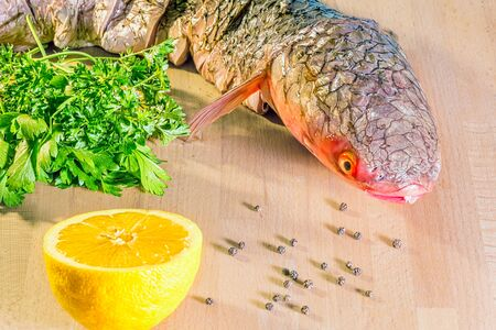 Fresh raw fish of red-finned mullet for cooking with lemon, parsley and spices on wooden background, close-up