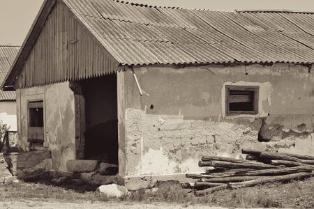 Ruined rural house and a pile of cut trees, sepia. Retro style  Reklamní fotografie