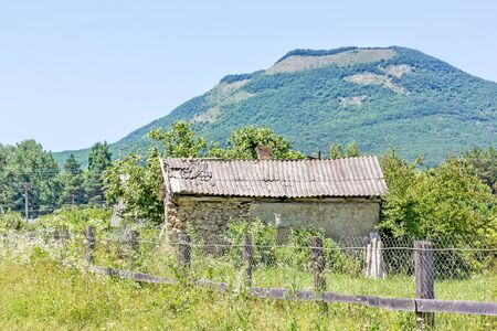 Dilapidated rural house in the thickets of weeds against the mountain and blue sky