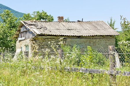 Dilapidated rural house in the thickets of weeds against the blue sky Reklamní fotografie