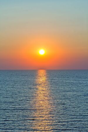 Scenic sunset and sun path in the blue sea on a summer evening