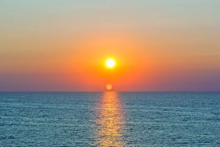 Scenic orange sunset and sun path in the blue sea on a summer evening