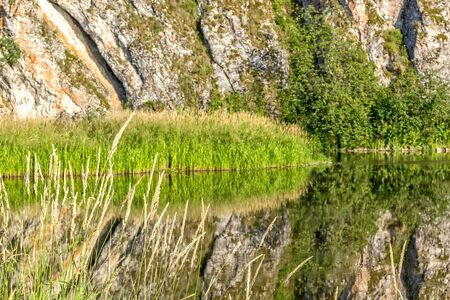 Scenic landscape with rock and reflection in the river on a quiet sunny summer evening, close-up