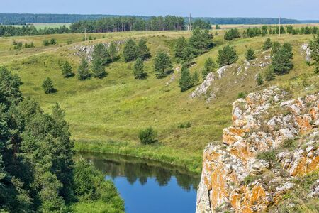 Scenic view from the cliff to the river, field and pine forest on a sunny summer day