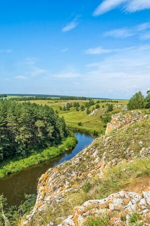 Scenic view from the cliff to the river, green field and pine forest on a sunny summer day 写真素材
