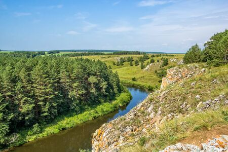 Scenic view from the cliff to the river, green field and pine forest on a background of blue sky with white clouds