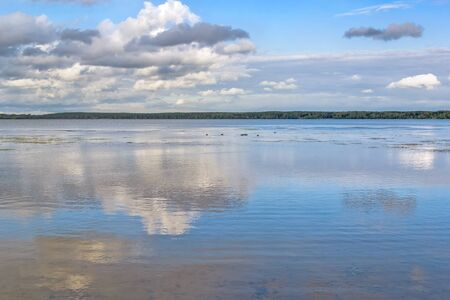 Picturesque landscape with a lake and reflection in the water of a blue sky and white clouds on a summer day 写真素材