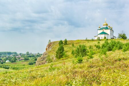 Landscape with the Church of the Kazan Icon of the Mother of God and the village of Aramashevo against a cloudy sky. Russia, Ural